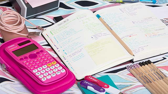 A calculator sits side-by-side with an open notebook.